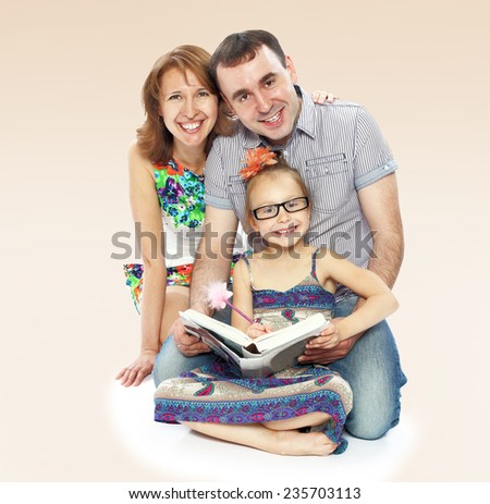 Happy young family mom dad and little daughter reading a book sitting on the floor. - stock photo