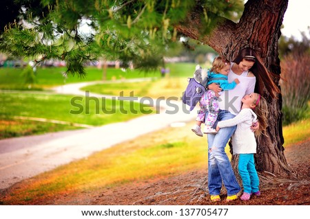happy young family mother and two daughters hugging and walking at beautiful park - stock photo