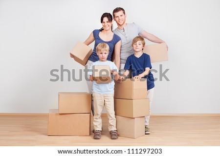 Happy young family moving into new house - stock photo
