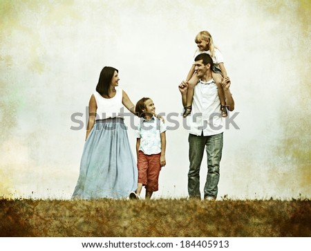 Happy young family of four members on green summer grass meadow having fun - stock photo