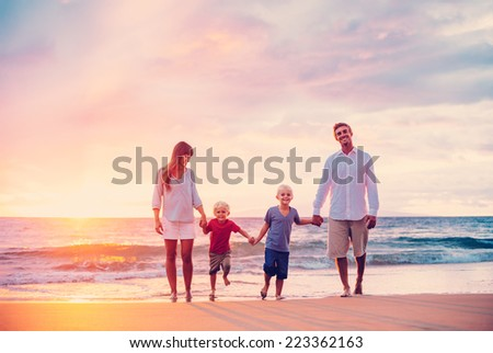 Happy Young Family of Four on the Beach at Sunset - stock photo