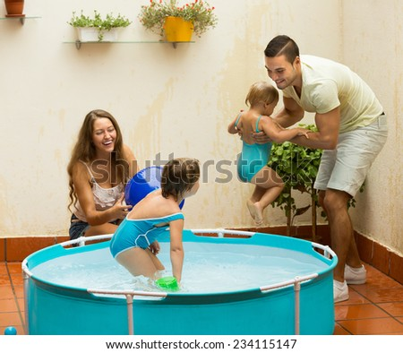 Happy young family of four playing in pool at terrace  - stock photo
