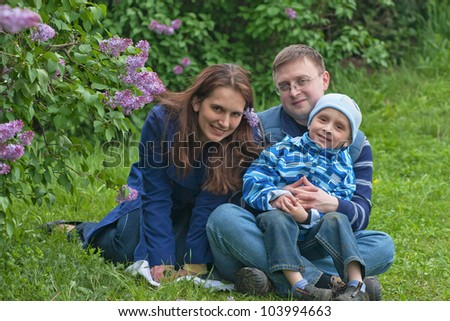 Happy young family of three have a rest in lilac garden - stock photo
