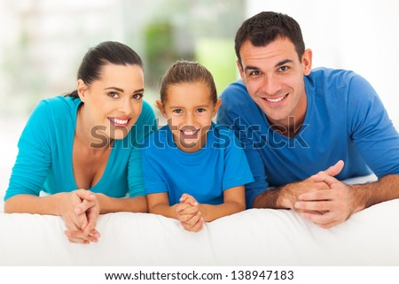 happy young family of three lying on bed at home - stock photo