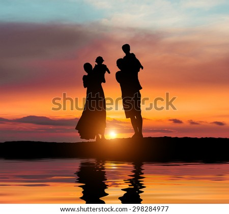 happy young family on a background of the magnificent sunset over the sea - stock photo