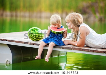 happy young family on picnic in the green park with lake - stock photo