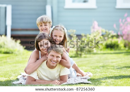 Happy young family outdoors - stock photo