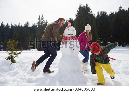 happy young  family playing in fresh snow and building snowman at beautiful sunny winter day outdoor in nature - stock photo