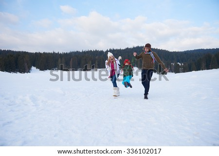 happy young  family playing in fresh snow  at beautiful sunny winter day outdoor in nature - stock photo