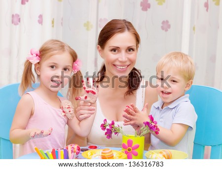 Happy young family playing with colorful paint at home, mother with two adorable children decorate Easter eggs - stock photo
