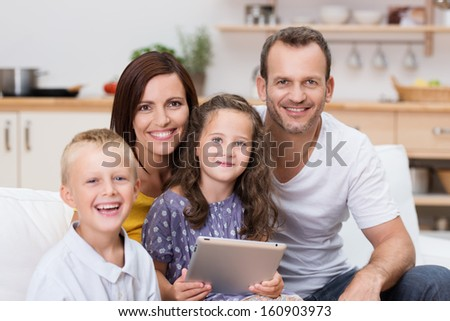 Happy young family relaxing with a tablet-pc with a young brother and sister and their two attractive young parents posing together in the living room - stock photo
