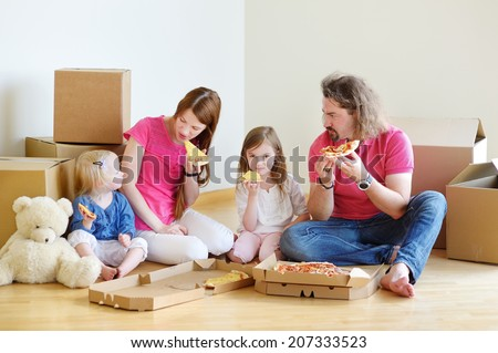 Happy young family sitting on a floor and eating pizza in their new home - stock photo