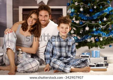 Happy young family sitting on floor at christmas morning in pajamas, smiling, looking at camera. - stock photo