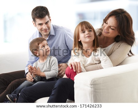 Happy young family sitting on sofa in living room - stock photo