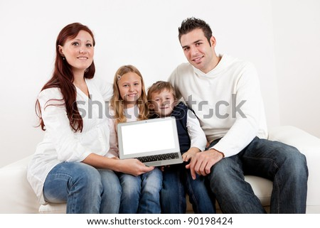 Happy young family sitting together in couch and presenting laptop - stock photo