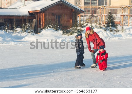 Happy young family skate at the rink in the winter. Beautiful family walking and playing on the ice in winter. - stock photo