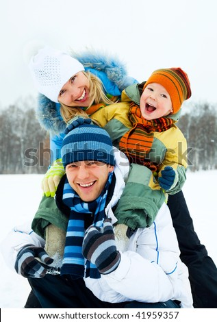 happy young family spending time outdoor in winter - stock photo
