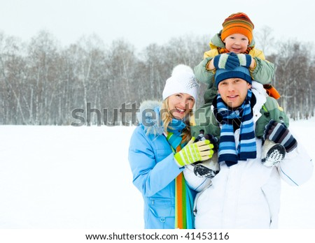 happy young family spending time outdoor in winter park (focus on the man) - stock photo