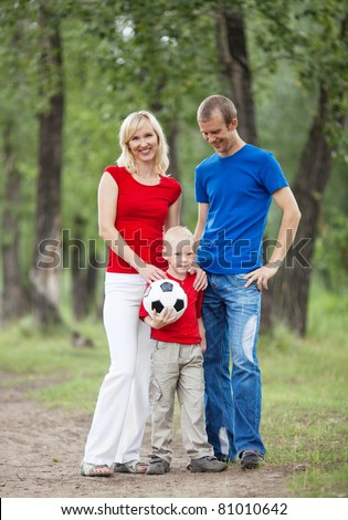 happy young family spending time outdoor on a summer day and playing ball(focus on the child) - stock photo