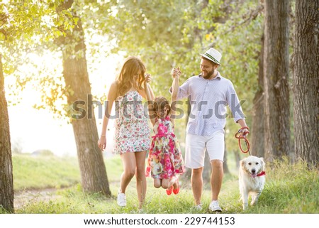 Happy young family spending time outdoor on a summer day with their dog - stock photo