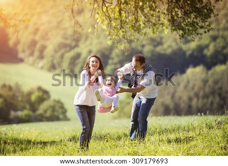 Happy young family spending time together outside in green nature       - stock photo