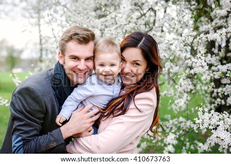Happy young family stands near a flowering tree and smiling - stock photo