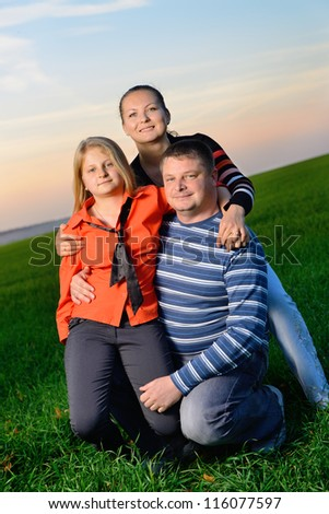 Happy young family. The green field and picturesque sky - stock photo