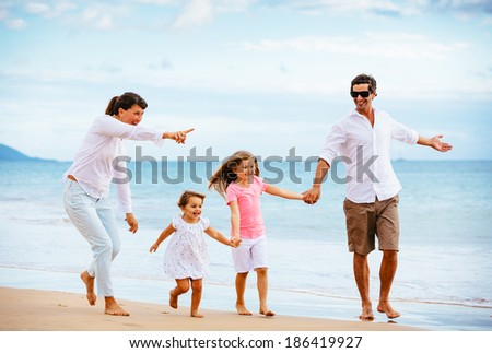 Happy young family walking on the beach at sunset. Happy Family Lifestyle  - stock photo