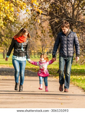 Happy young family walks in the park - stock photo