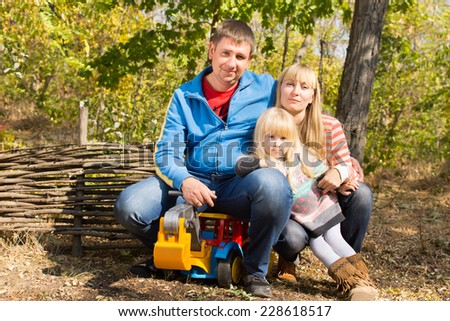 Happy young family with a mother , father and their pretty blond daughter posing together with a toy dump truck outdoors in woodland in the sunshine against a rustic wooden fence - stock photo