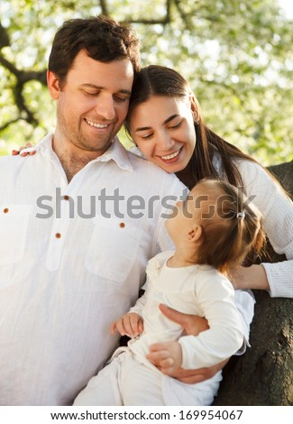 Happy young family with baby girl in the spring park - stock photo