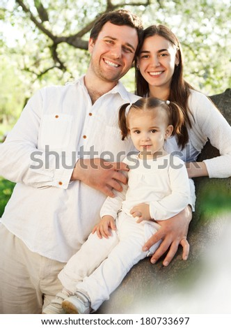 Happy young family with baby girl outdoors. Spring - stock photo