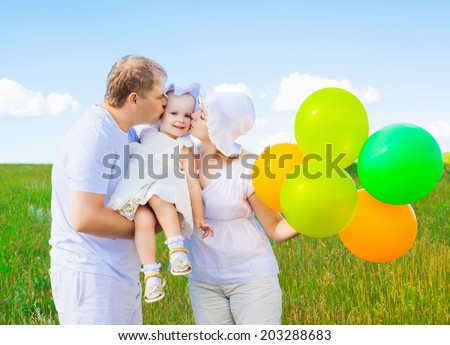 happy young family with balloons outdoor on a summer day - stock photo
