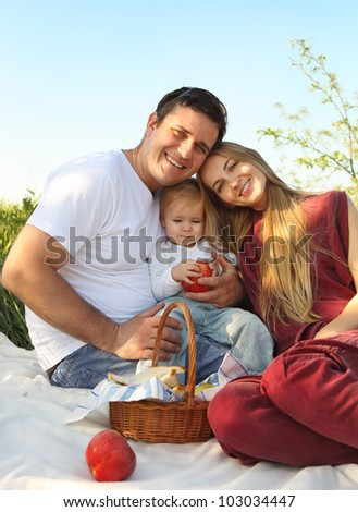 Happy young family with child on summer picnic - stock photo