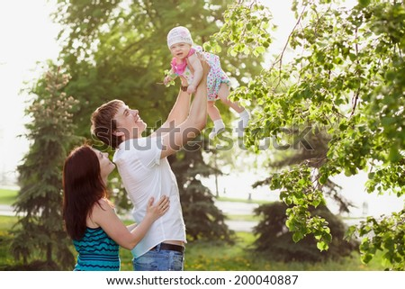 Happy young family with child resting outdoors in summer park - stock photo