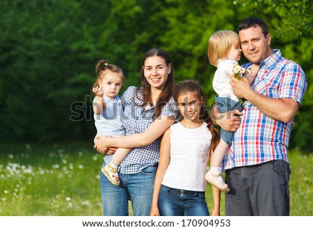 Happy young family with children in the spring forest - stock photo