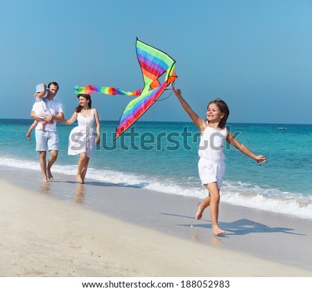 Happy young family with flying a kite on the beach - stock photo