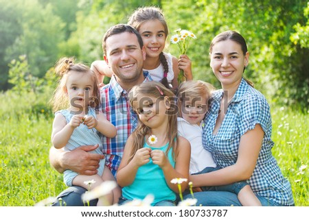 Happy young family with four children in the spring forest - stock photo