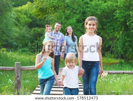 Happy young family with four children outdoors - stock photo