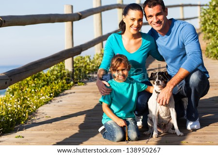 happy young family with pet dog at the beach - stock photo