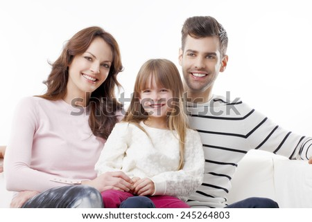 Happy young family with preschool daughter sitting at sofa. Isolated on white background. - stock photo