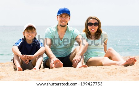 Happy young family with son spending free time on the beach - stock photo