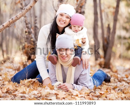 happy young family with their daughter spending time outdoor in the autumn park  (focus on the man) - stock photo