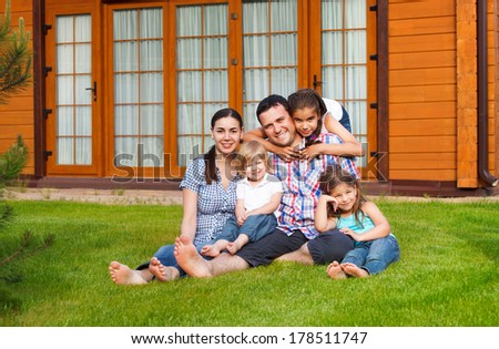Happy young family with three children near the house - stock photo