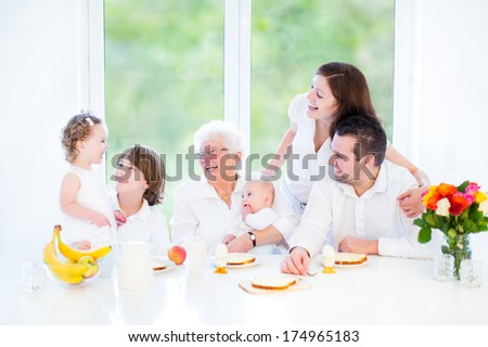 Happy young family with three children - teenager boy, adorable curly toddler girl and newborn baby having fun at breakfast with their grandmother in a white dining room with a big garden view window - stock photo