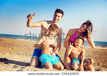 Happy young family with two boys on a tropical beach kneeling in the golden sand laughing and giving V-signs and thumbs up to show their approval of the summer sunshine and idyllic seashore - stock photo