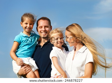 Happy young family with two children outdoors. Summertime - stock photo