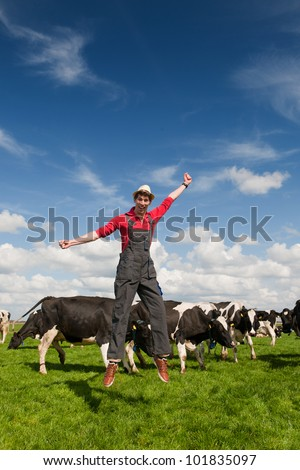 Happy young farmer jumping in field with cows - stock photo
