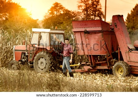 Happy young farmer waving hand in front of tractor harvesting corn - stock photo