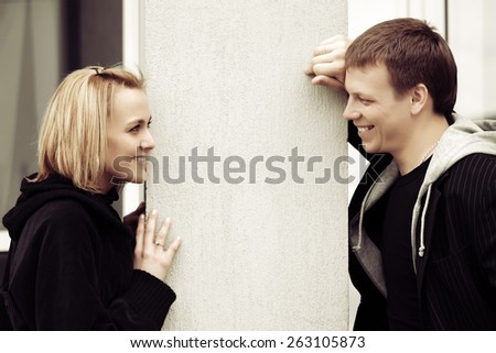 Happy young fashion couple flirting on a city street - stock photo